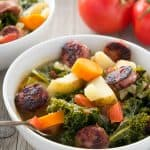 Sausage Potato Kale Soup in bowl with tomatoes in background.