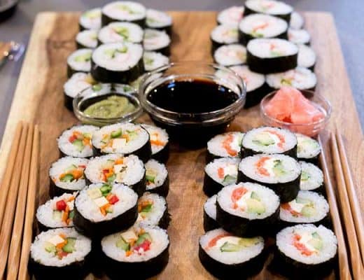 Sushi, soy sauce and chopsticks on wooden serving platter.
