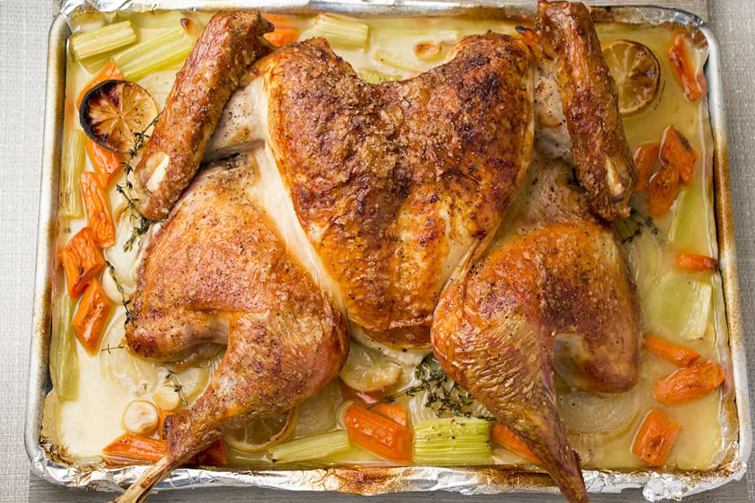 Spatchcock turkey on baking sheet with aromatics.