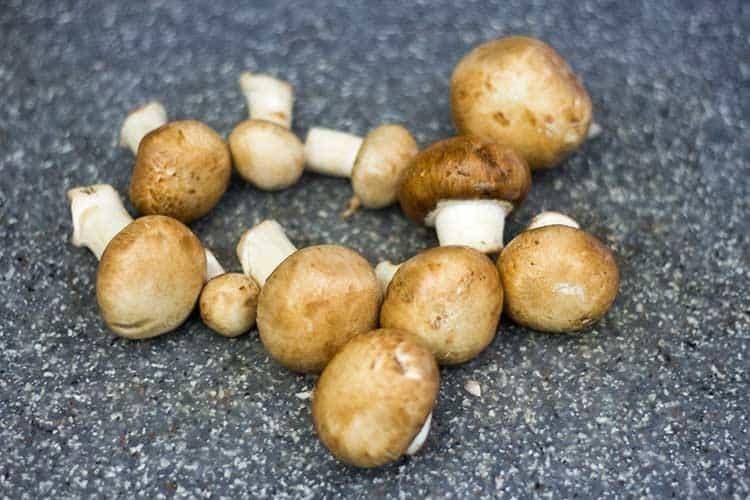 whole baby bella mushrooms on cutting board