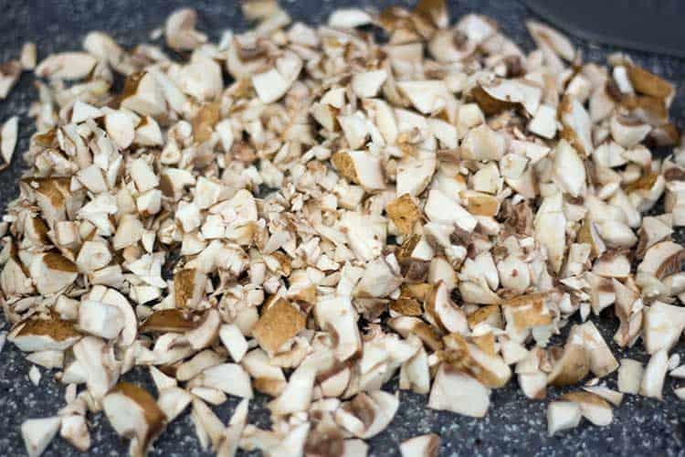 Baby bella mushrooms diced on cutting board