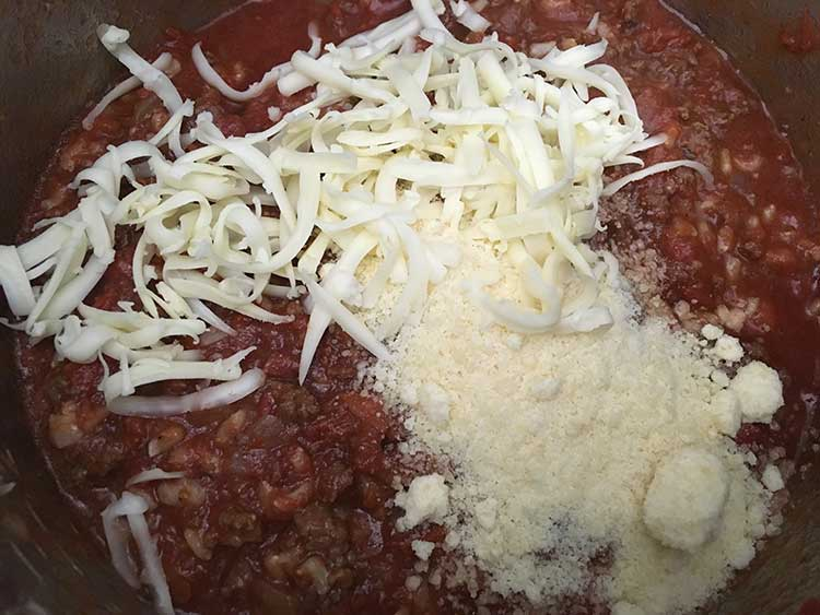 Sauce mixture topped with fontina and parmesan cheeses.