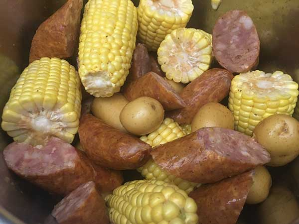 Uncooked corn, sausage, and potatoes in Instant Pot.
