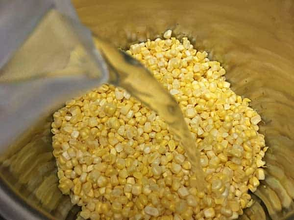 Poring water into pot with corn kernels.
