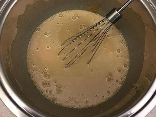 Sugar, eggs, milk and butter mixture in bowl with whisk.