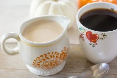 Pumpkin spice creamer in creamer dish, next to a cup of black coffee.