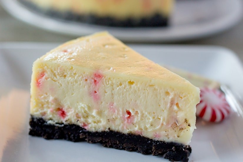 A slice of white chocolate peppermint bark cheesecake on a white plate with a piece of peppermint bark and a starlight mint.