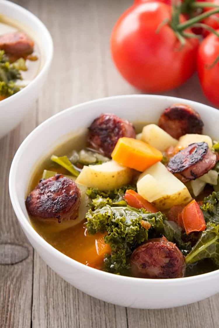 Sausage, Potato and Kale Soup in bowl with tomatoes in background