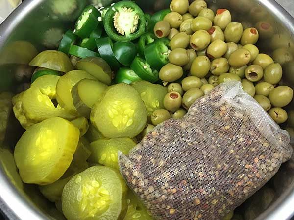 Pickles, jalapenos, olives, and crab boil in Instant Pot.