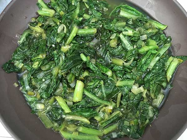 cooked turnip greens in brown bowl
