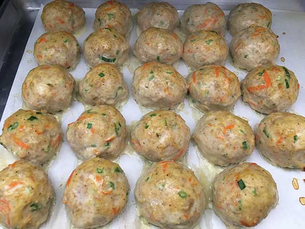 chicken and sausage meatballs on parchment paper