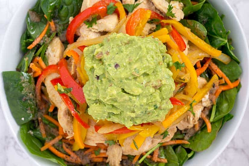 fajitas salad topped with guacamole in white bowl