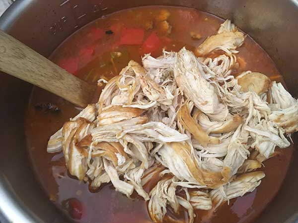 Shredded chicken on top of gumbo soup.