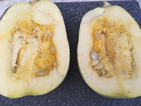 spaghetti squash cut in half on cutting board