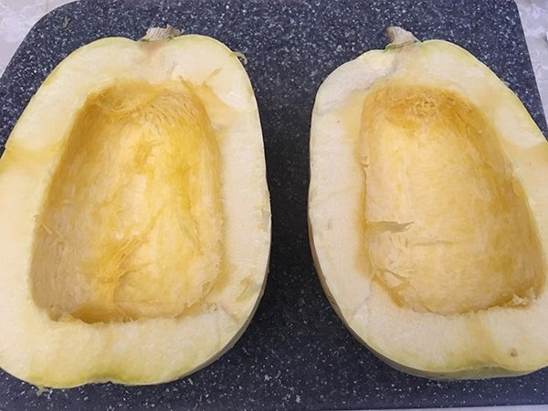 spaghetti squash cut in half on cutting board with seeds removed