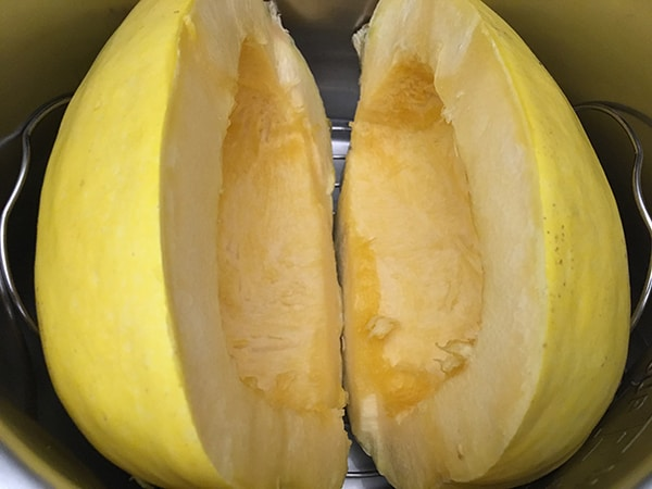 two uncooked spaghetti squash halves in Instant Pot
