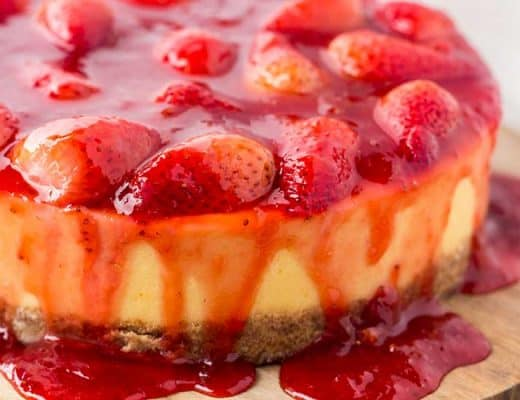 Strawberry-covered cheesecake on wood cutting board