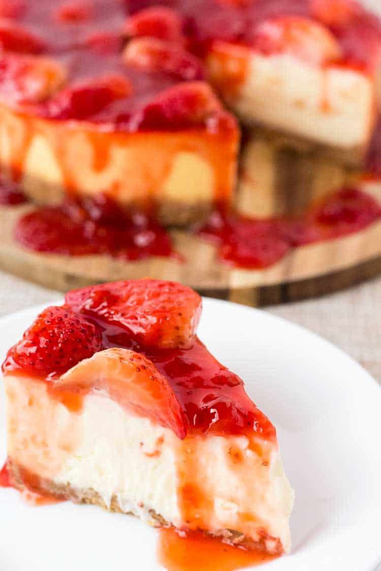 Slice of strawberry covered cheesecake on white plate.