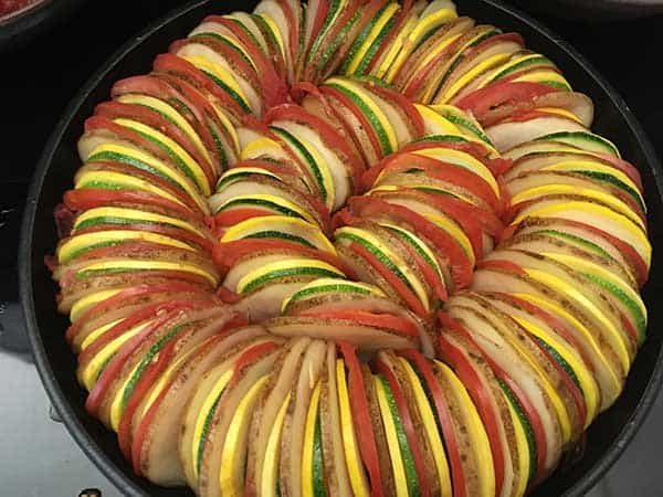 thinly sliced potatoes, tomatoes, zucchini, and squash in ratatouille pattern