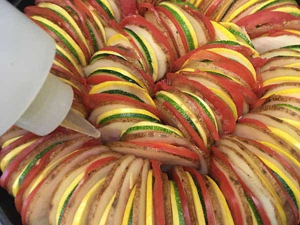 thinly sliced potatoes, tomatoes, zucchini, and squash in ratatouille pattern with plastic bottle