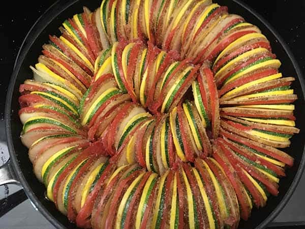 thinly sliced potatoes, tomatoes, zucchini, and squash in ratatouille pattern topped with sea salt