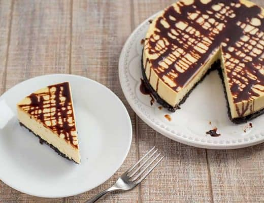 Slice and whole Bailey's Irish Cream cheesecake on white plates topped with chocolate sauce.