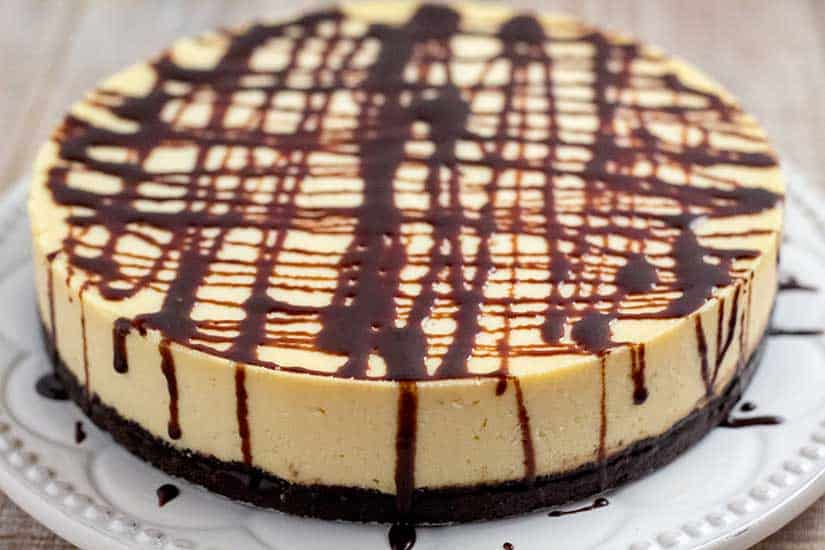 Whole Bailey's Irish Cream cheesecake on white plate topped with chocolate sauce.