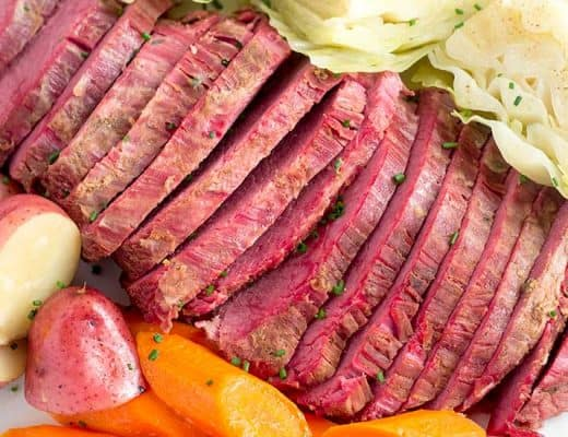 sliced corned beef brisket on serving platter with cabbage, potatoes, and carrots.