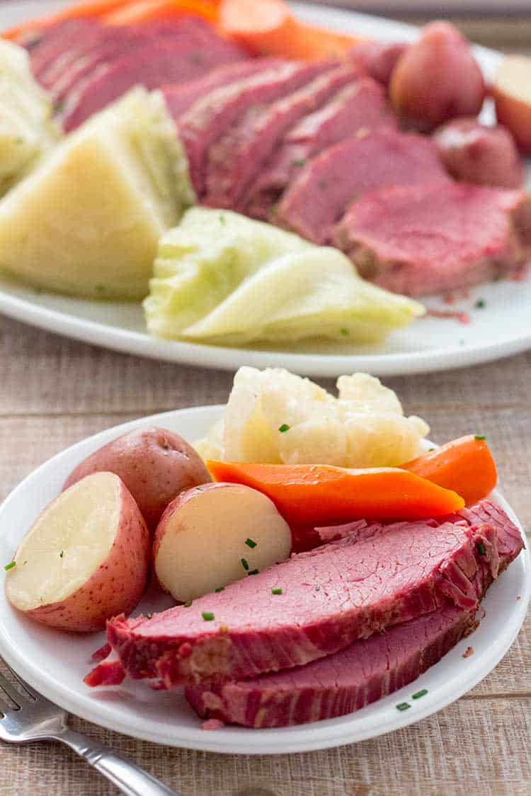 sliced corned beef brisket on small plate with cabbage, potatoes, and carrots with platter in background.