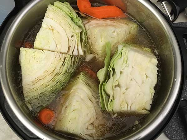Cabbage wedges on top of broth and other veggies.