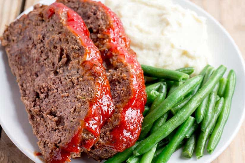 sliced meatloaf on white plate with mashed potatoes and green beans