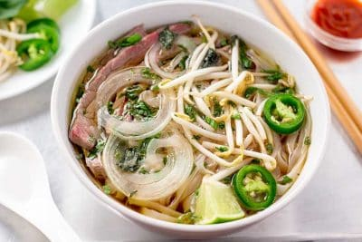 Beef pho in white bowl.