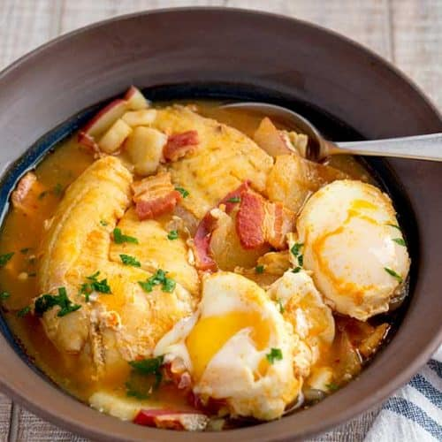 Fish stew in brown bowl.