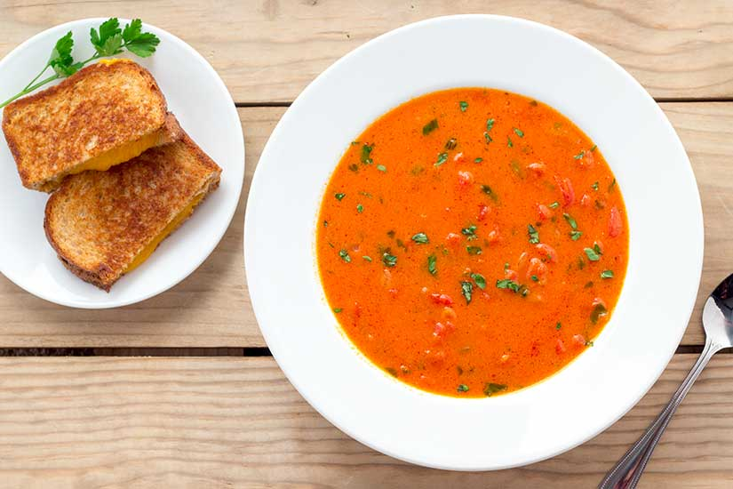 Tomato basil soup in white bowl with grilled cheese on side plate.