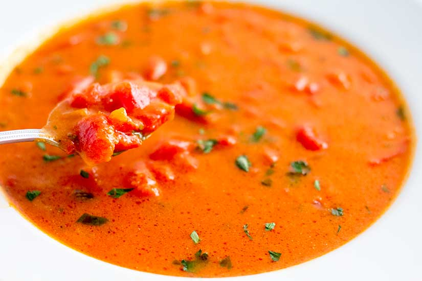 Tomato basil soup in white bowl with spoon.