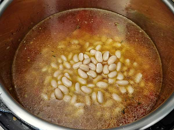 Vegetable broth in pot with aromatics and white beans.