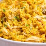 Arroz con pollo in white casserole dish.