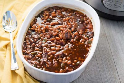 Baked beans in white casserole dish.
