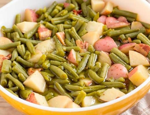 Green beans with potatoes and bacon in yellow bowl.