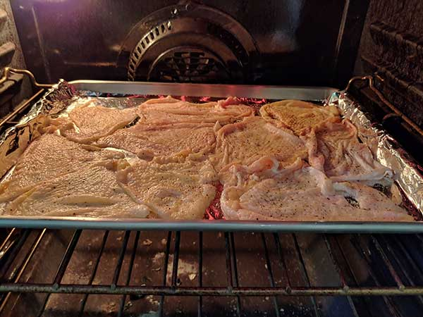 Chicken skins on baking sheet in oven.