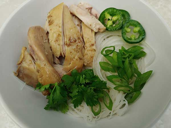 Chicken, herbs, and onions on rice noodles in white bowl.