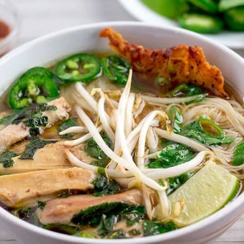 Pho ga in white bowl with garnishes in background.