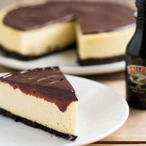 Slice of cheesecake, covered in chocolate sauce, on plate next to a small bottle of Bailey's.