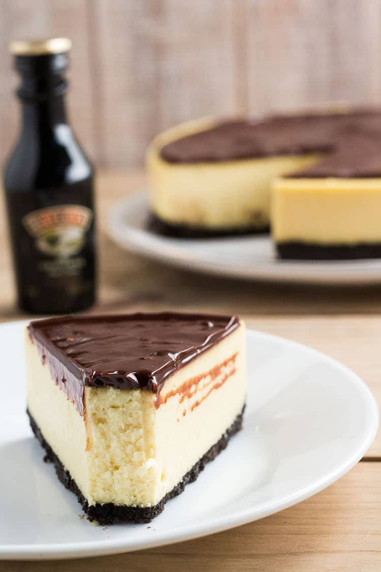 Slice of cheesecake, covered in chocolate sauce, in front of small bottle of Bailey's.