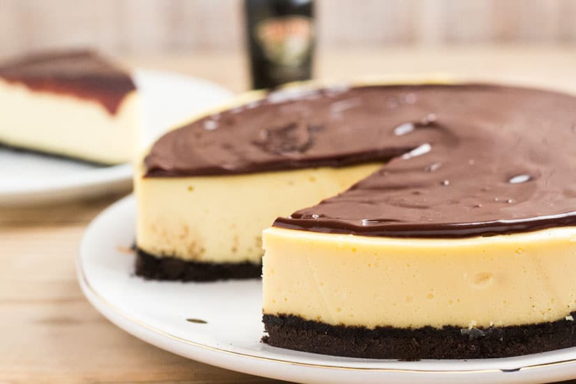 Whole cheesecake, covered in chocolate, with one slice removed.