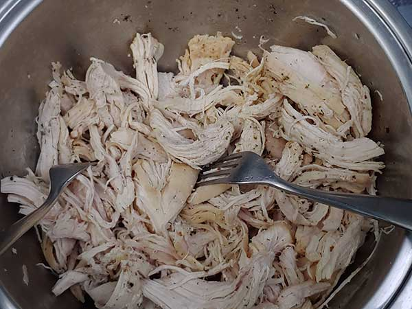 Shredding chicken in bowl with two forks.