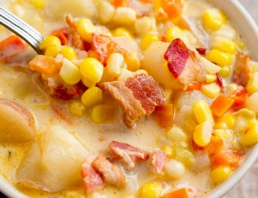 Close up of corn chowder in white bowl with spoon.