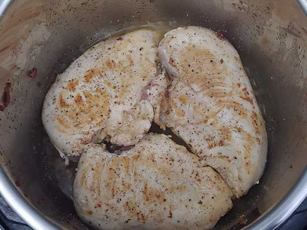 Browning chicken breasts in pot.