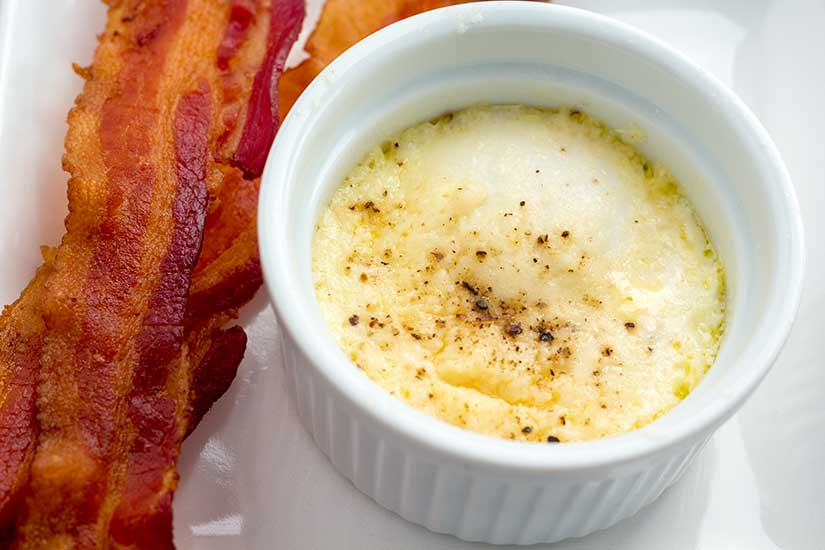 Baked eggs in ramekin with bacon on the side.