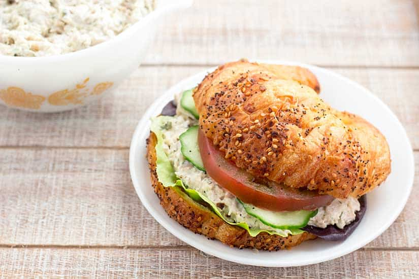 Chicken salad sandwich on croissant with tomato and cucumbers.
